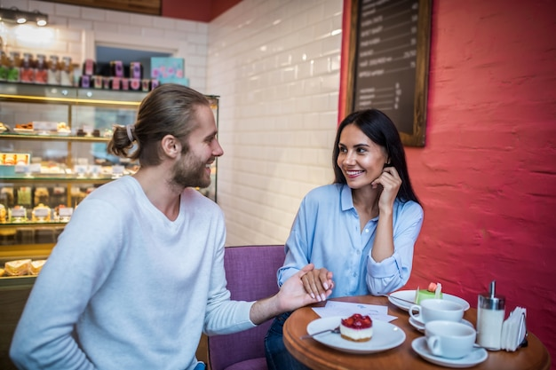 Verloofd paar met huwelijksuitnodigingen in een café