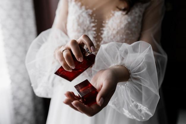 Verloofde in witte modieuze jurk met mooie mouwen en parfum in handen