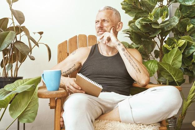 Verloren in gedachten gefocuste man van middelbare leeftijd zittend op het zonnige terras van zijn moderne appartement