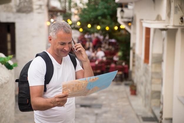 Verloren toerist die op de kaart van de stad op een reis kijkt. op zoek naar routebeschrijving.