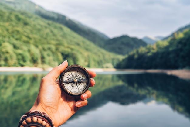 Verloren vrouw op de berg, zich oriënteren met een kompas. een oplossing vinden.