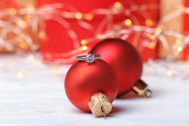 Verlovingsring en kerstballen op tafel, close-up