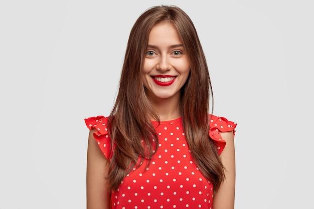 Vermaakte brunette vrouw met donker haar, draagt rode lippenstift, gekleed in modieuze polka dot jurk