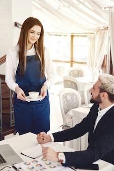 Vermakelijk gesprek tussen zakenman en een serveerster in het restaurant