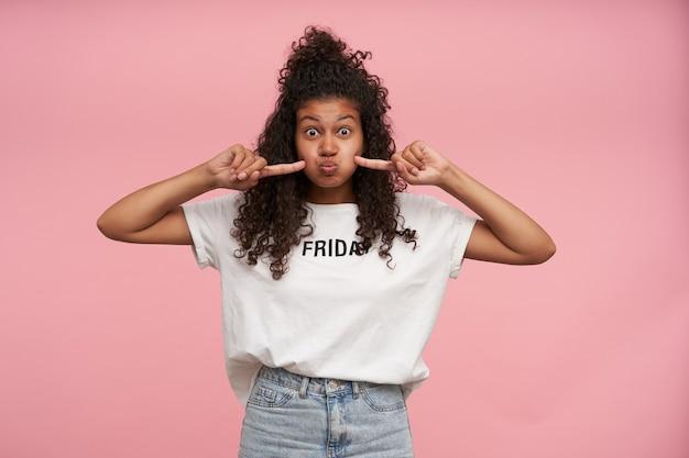 Vermakelijk portret van jonge krullende donkere huid brunette vrouw puffend uit wangen en ronde ogen met opgetrokken wenkbrauwen, wit t-shirt en spijkerbroek dragen op roze