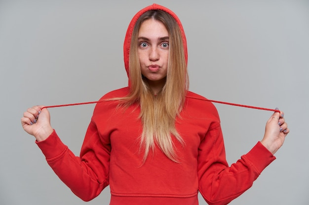 Vermakelijke schattige blonde jonge vrouw in rode hoodie grappig gezicht maken en plezier maken over grijze muur