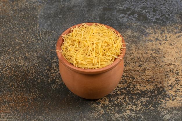 Vermicelli in een kom van klei, op de marmeren tafel.