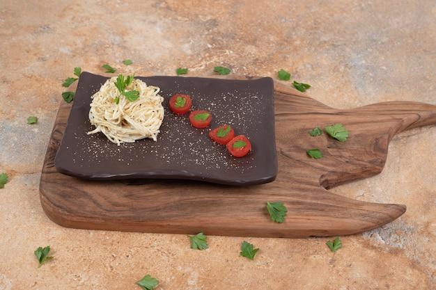 Vermicelli met peterselie en tomaten op zwarte plaat. hoge kwaliteit illustratie