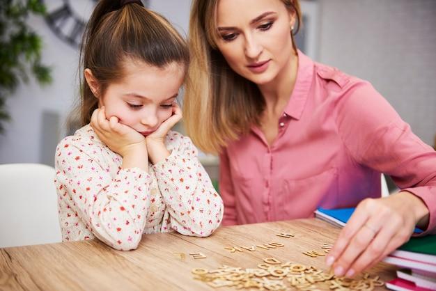 Vermoeid en verveeld kind en haar moeder die thuis aan het studeren is