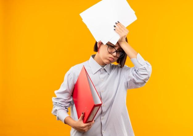 Vermoeid jong call centreermeisje die glazen dragen die omslag en documenten boven het hoofd houden neerkijkt geïsoleerd op oranje muur