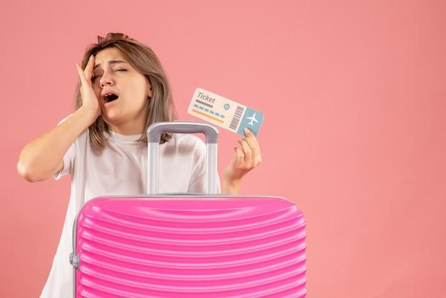 Vermoeid jong meisje met roze koffer met ticket hand op haar hoofd zetten