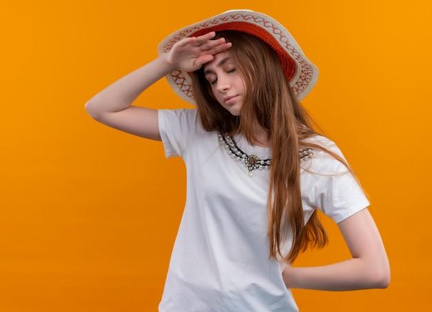 Vermoeid jong reizigersmeisje dat hoed draagt en handen op voorhoofd en achter haar rug op geïsoleerde oranje muur legt