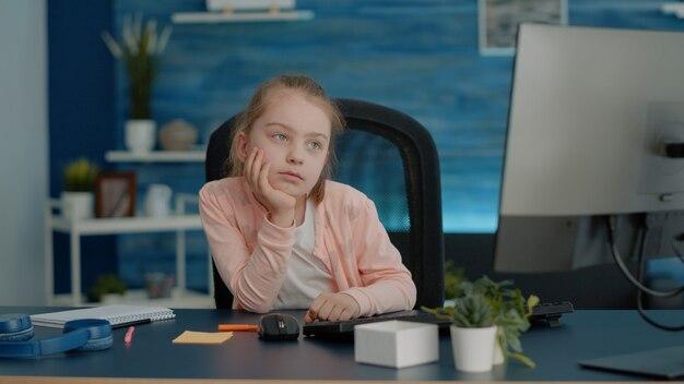 Vermoeid kind dat online les op de computer bijwoont