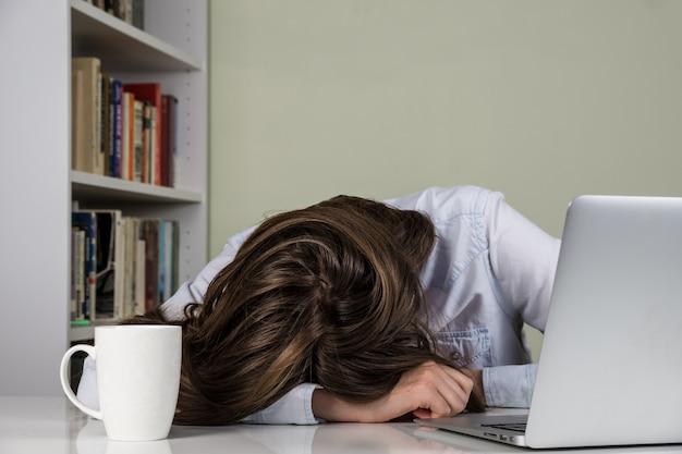 Vermoeid meisje dat haar hoofd rust op de lijst van het werken met computer