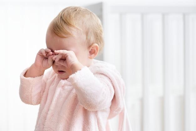 Vermoeid meisje huilt en wrijft in haar ogen