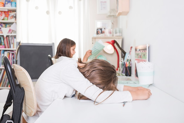 Vermoeid meisje tijdens thuiswerkvoorbereiding