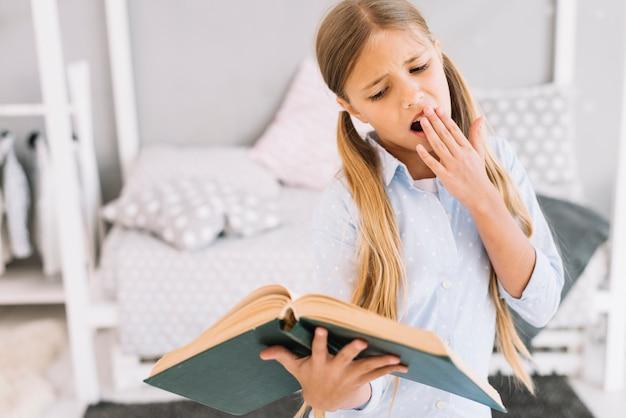 Vermoeid mooi meisje dat een boek leest