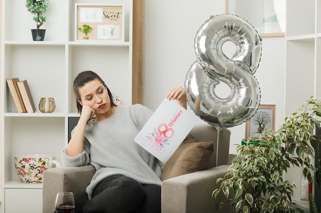 Vermoeid mooi meisje op een gelukkige vrouwendag die een wenskaart vasthoudt en bekijkt terwijl ze op een fauteuil in de woonkamer zit