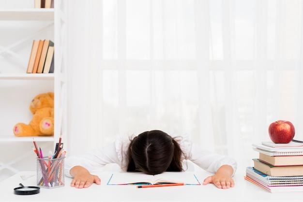 Vermoeid schoolmeisje dat over voorbeeldenboek ligt