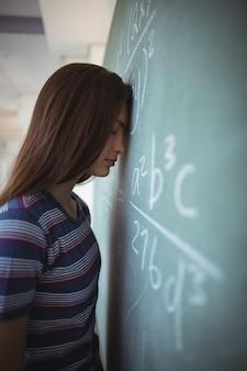 Vermoeid schoolmeisje dat zich met gesloten ogen dichtbij bord in klaslokaal bevindt