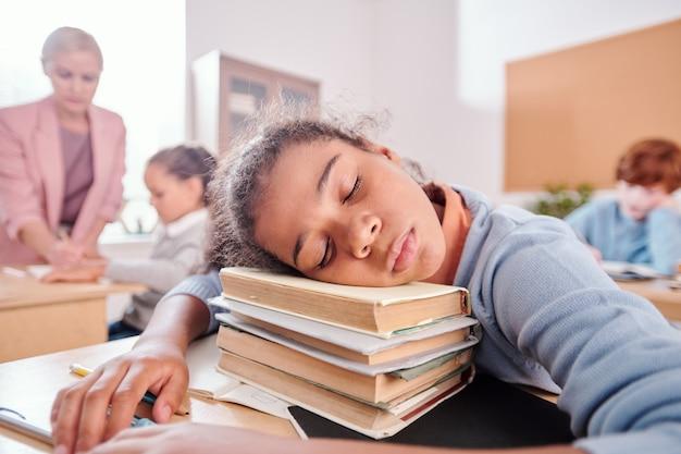 Vermoeid schoolmeisje in vrijetijdskleding die het hoofd op een stapel boeken houdt terwijl ze een dutje doet bij het bureau tijdens de les