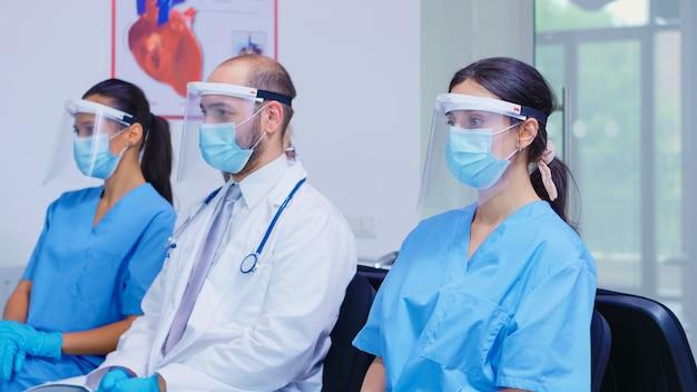 Vermoeid team van medisch personeel met gezichtsmasker en vizier tegen uitbraak van het coronavirus in de wachtruimte van het ziekenhuis. patiënt die in de ziekenhuislobby binnenkomt. dokter die een stethoscoop draagt.