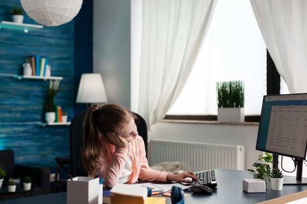 Vermoeid uitgeput schoolmeisje dat wiskundehuiswerk doet dat online cursus analyseert