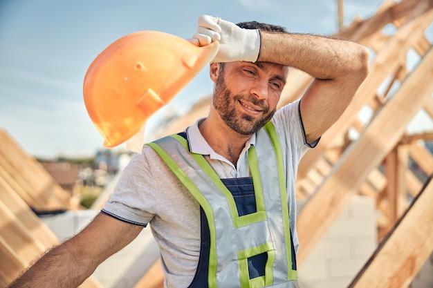 Vermoeid uitziende bouwer die zijn helm vasthoudt en het zweet van zijn voorhoofd veegt terwijl hij op de bouwplaats staat