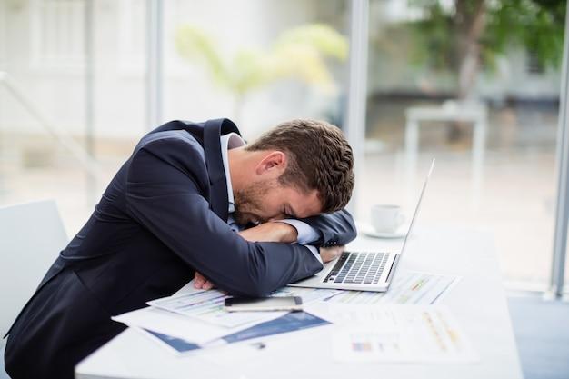 Vermoeid zakenman rustend hoofd op laptop bij bureau