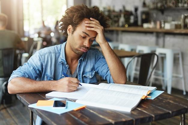 Vermoeide afro-amerikaanse student met krullend kapsel dat zijn wangen uitblaast en er verveeld of beu uitziet, geduld verliest terwijl hij geen ingewikkeld wiskundig probleem oplost, thuisopdracht doet
