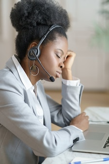 Vermoeide afro-kantoormedewerker met koptelefoon slaapt op de werkplek en lijdt aan chronische vermoeidheid