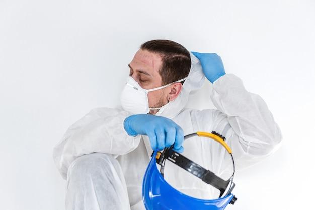 Vermoeide arts die een beschermend kostuum draagt om pandemie van het coronavirus te bestrijden