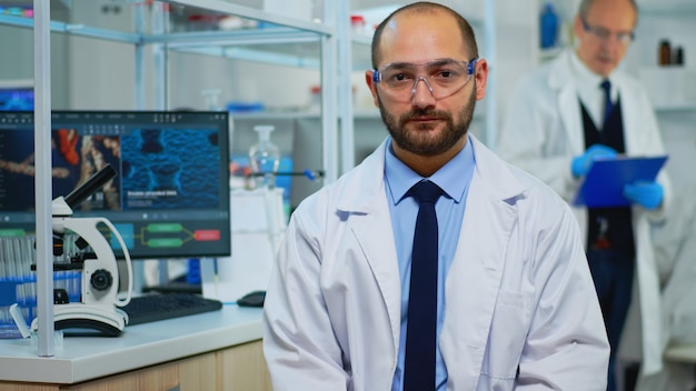 Vermoeide arts die uitgeput naar de camera kijkt in een modern uitgerust laboratorium. multi-etnisch team dat virusevolutie onderzoekt met behulp van hightech- en scheikundige hulpmiddelen voor wetenschappelijk onderzoek, vaccinontwikkeling.