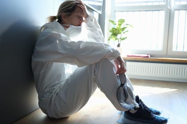 Vermoeide arts in beschermend antipestpak zittend op de gang van de kliniek. emotionele burn-out van medisch personeel tijdens covid-19 pandemieconcept
