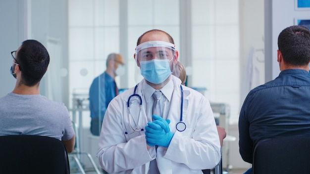 Vermoeide arts met gezichtsmasker en vizier tegen coronavirus in de wachtruimte van het ziekenhuis, kijkend naar de camera. senior man en verpleegster in de onderzoekskamer van het ziekenhuis.