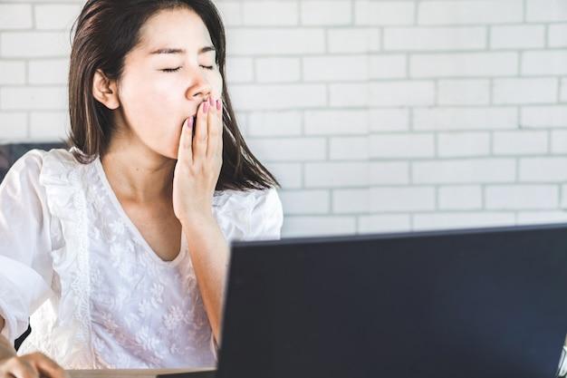 Vermoeide aziatische vrouw die op het werk geeuwt