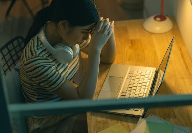 Vermoeide aziatische vrouw die 's nachts haar werk probeert te doen