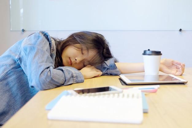 Vermoeide aziatische vrouwenslaap bij bureau.