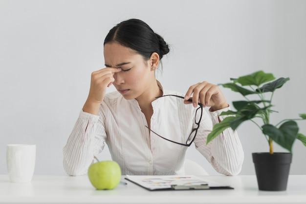 Vermoeide aziatische vrouwenzitting in het bureau