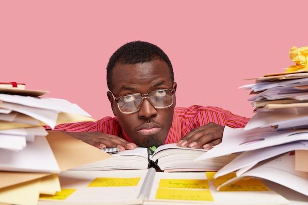 Vermoeide, bedachtzame, donkere man kijkt naar boven, draagt een bril met dikke lenzen, houdt zijn handen op geopende agenda, bezig met het bestuderen van papieren documenten