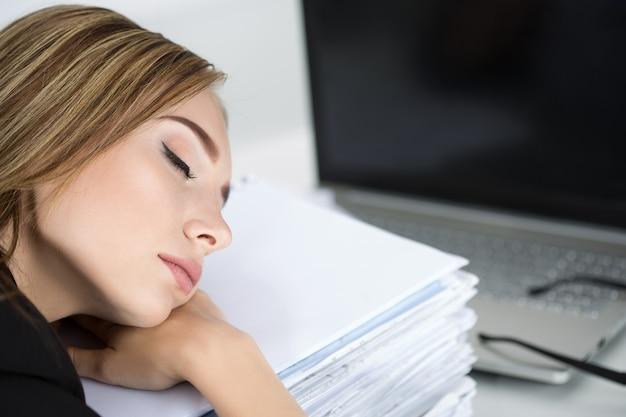 Vermoeide bedrijfsvrouw die op hoop documenten op haar werkplek slaapt. overwerk, overwerk en stress op het werk concept.
