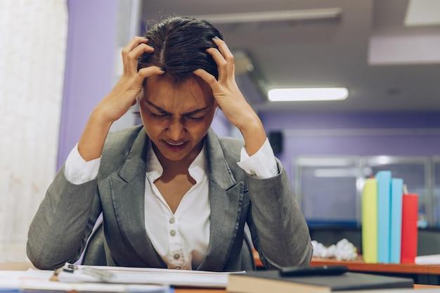 Vermoeide bedrijfsvrouw met hoofdpijn op kantoor