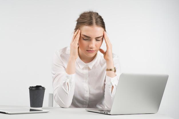 Vermoeide bedrijfsvrouwenzitting achter laptop met een kop van koffie en ipad op de lijst en wat betreft haar hoofd voor handen