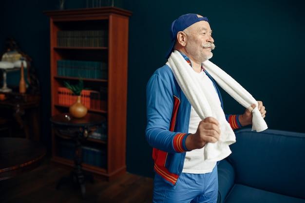 Vermoeide bejaarde sportman in uniform na training