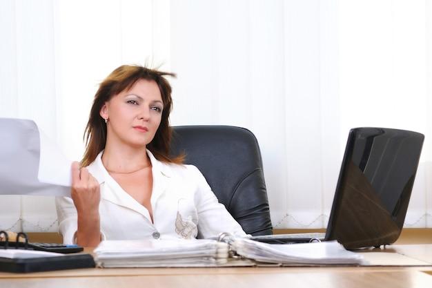 Vermoeide blanke blanke vrouw in pak zittend aan een bureau