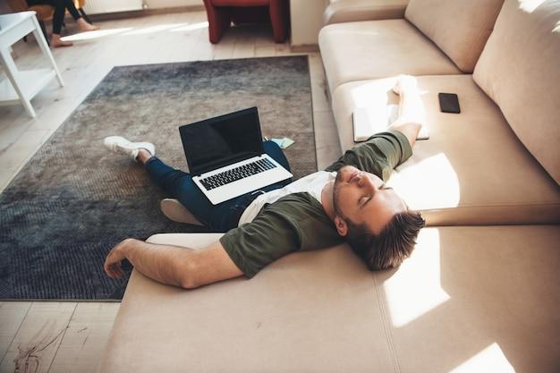 Vermoeide blanke man liggend op de vloer met een laptop in slaap vallen na online werken