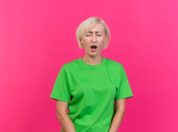 Vermoeide blonde slavische vrouw van middelbare leeftijd geeuwen met gesloten ogen geïsoleerd op karmozijnrode achtergrond met kopie ruimte