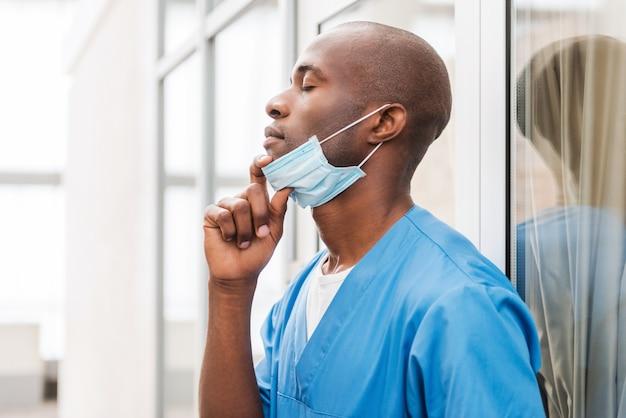 Vermoeide chirurg. zijaanzicht van een jonge afrikaanse arts in blauw uniform die een chirurgisch masker afzet en de ogen gesloten houdt terwijl hij tegen de glazen deur leunt