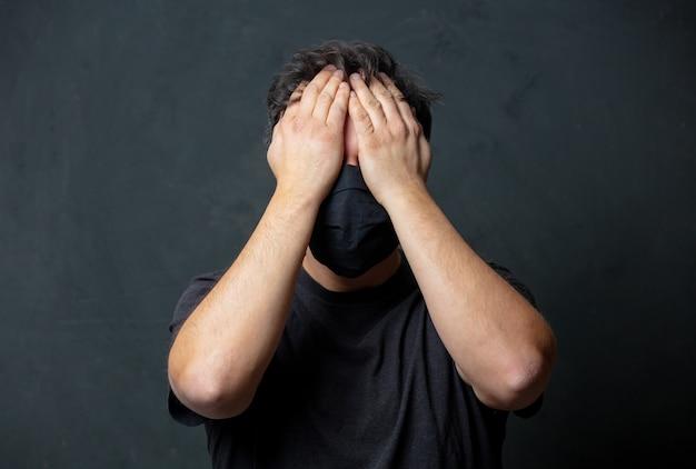 Vermoeide donkerbruine man in zwarte gezichtsmasker op donkere muur