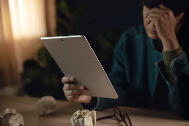 Vermoeide en beklemtoonde persoon zitting op bureau met tablet binnenshuis. hand op hoofd. depressief van werk of een crisis